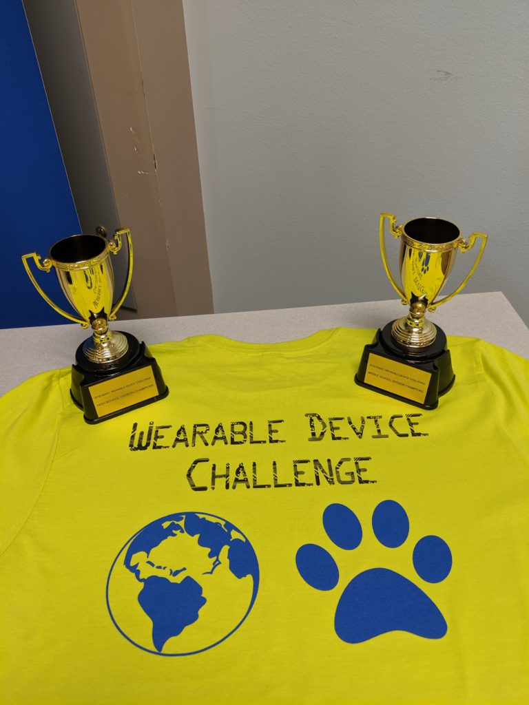 Wearable Device Challenge t-shirt and winning trophies.